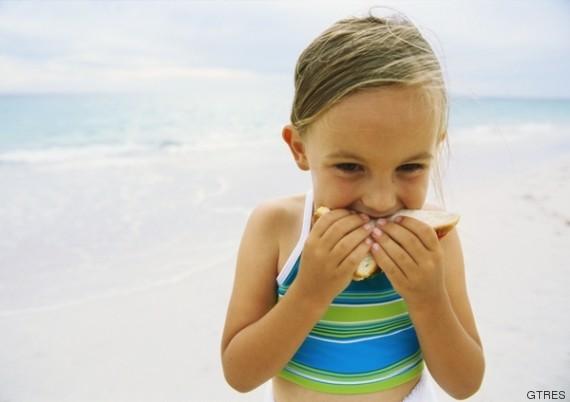 niñas comiendo bocadillo en la playa