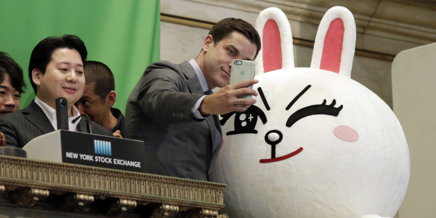 New York Stock Exchange President Tom Farley, center, takes a selfie with Line character Cony on the bell podium at the NYSE, Thursday, July 14, 2016. Line Chief Strategy & Marketing Officer Jun Masuda is at left, before his company's IFO.