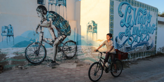 A Tunisian boy cycles past street art in Erriadh, a village on the resort island of Djerba, south of Tunis, Tunisia, Wednesday, Oct. 28, 2015. (AP Photo/Mosa'ab Elshamy)