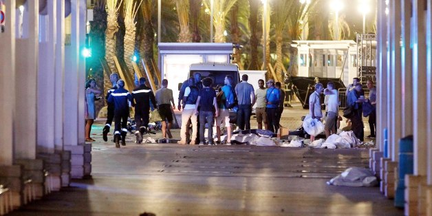 People stand next to covered bodies in the early hours of Friday, July 15, 2016, on the Promenade des Anglais in Nice, southern France.  France has been stunned again as a large white truck killed many people after it mowed through a crowd of revelers gathered for a Bastille Day fireworks display late Thursday evening, in the Riviera city of Nice. (AP Photo)