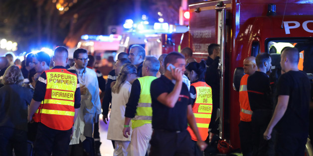 Police officers, firefighters and rescue workers are seen at the site of an attack on the Promenade des Anglais on July 15, 2016, after a truck drove into a crowd watching a fireworks display in the French Riviera town of Nice.A truck ploughed into a crowd in the French resort of Nice on July 14, leaving at least 60 dead and scores injured in an 'attack' after a Bastille Day fireworks display, prosecutors said on July 15.  / AFP / Valery HACHE        (Photo credit should read VALERY HACHE/AFP/Ge