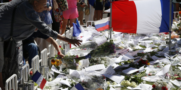 A woman adds a bouquet of flowers near French flags placed in tribute to victims, two days after an attack by the driver of a heavy truck who ran into a crowd on Bastille Day killing scores and injuring as many on the Promenade des Anglais, in Nice, France, July 16, 2016.  REUTERS/Pascal Rossignol
