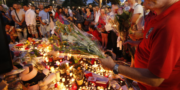 People gather to leave flowers in tribute to victims the day after a truck ran into a crowd at high speed killing scores and injuring more on the Promenade des Anglais who were celebrating the Bastille Day national holiday, in Nice, France, July 15, 2016.  REUTERS/Eric Gaillard