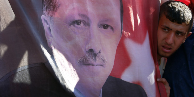A Turkish man looks towards a portrait of Turkish President Recep Tayyip Erdogan during a protest against the military coup outside Turkey's parliament near the Turkish military headquarters in Ankara, Turkey, Saturday, July 16, 2016. Forces loyal to Turkey's President Recep Tayyip Erdogan quashed a coup attempt in a night of explosions, air battles and gunfire that left dozens dead Saturday. (AP Photo/Hussein Malla)
