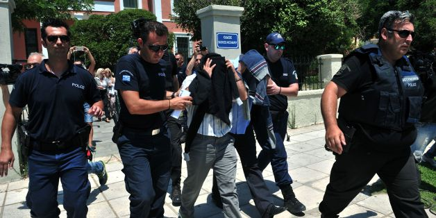 Turkish officers escorted by Greek police officers leave the courthouse of Alexandroupoli after appearing before a Greek prosecutor, on July 17, 2016.  Eight Turkish military personnel who fled to Greece by helicopter after July 15 failed coup took no part in the putsch, their lawyer said, although a Greek government spokeswoman contradicted their account. The eight, who have claimed asylum in Greece, arrived by military helicopter on July 16, 2016 after sending a distress signal to authorities