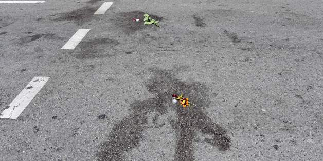 TOPSHOT - A picture taken on July 16, 2016 in Nice shows flowers placed on blood stains of victims of the deadly attack on the Promenade des Anglais seafront during Bastille Day.The Islamic State group claimed responsibility for the truck attack that killed 84 people in Nice on France's national holiday, a news service affiliated with the jihadists said Saturday. Tunisian Mohamed Lahouaiej-Bouhlel, 31, smashed a 19-tonne truck into a packed crowd of people in the Riviera city celebrating Bastill