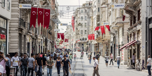 Banners of the Turkish national flag hang above pedestrians passing along a half empty Taksim street in Istanbul, Turkey, on Monday, July 18, 2016. Tourism is an essential source of foreign currency to finance Turkey's current-account deficit and employs 8 percent of the nation's workforce. Photographer: Ismail Ferdous/Bloomberg via Getty Images