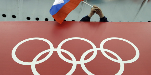FILE - In this Feb. 18, 2014, file photo, a Russian skating fan holds the country's national flag over the Olympic rings before the start of the men's 10,000-meter speedskating race at Adler Arena Skating Center during the 2014 Winter Olympics in Sochi, Russia. On Monday, July 18, 2016 WADA investigator Richard McLaren confirmed claims of state-run doping in Russia. (AP Photo/David J. Phillip, File)