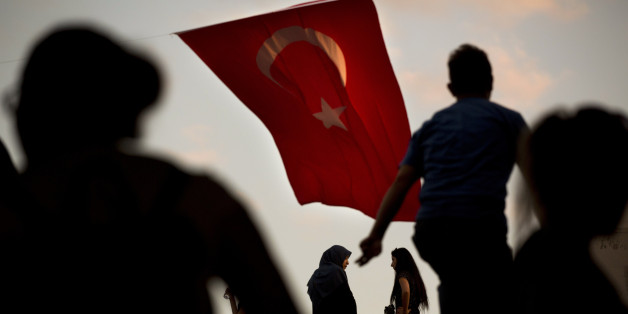 People walk by a Turkish flag in central Istanbul, Monday, July 18, 2016. Turkey's Interior Ministry has fired nearly 9,000 police officers, bureaucrats and others and detained thousands of suspected plotters following a foiled coup against the government, Turkey's state-run news agency reported Monday. (AP Photo/Emilio Morenatti)