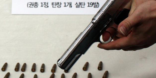 부산경찰청 마약수사대가 부산으로 잠입한 일본 조직폭력단(야쿠자) 조직원에게서 압수한 권총과 실탄. 경찰이 19일 방아쇠를 당겨 격발을 시연하고 있다.