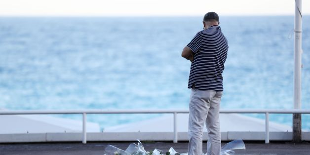 A man passes a make-shift memorial for victims of the deadly Bastille Day attack on July 16, 2016 in Nice.The Islamic State group claimed responsibility for the truck attack that killed 84 people in Nice on France's national holiday, a news service affiliated with the jihadists said on July 16. Tunisian Mohamed Lahouaiej-Bouhlel, 31, smashed a 19-tonne truck into a packed crowd of people in the Riviera city celebrating Bastille Day -- France's national day. / AFP / Valery HACHE        (Photo cre