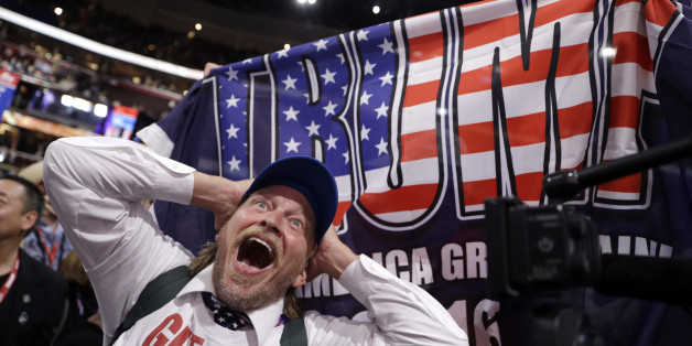 California delegate Jake Byrd reacts as New York delegate Bob Hayssen holds up a Trump flag during the second day session of the Republican National Convention in Cleveland, Tuesday, July 19, 2016. (AP Photo/John Locher)