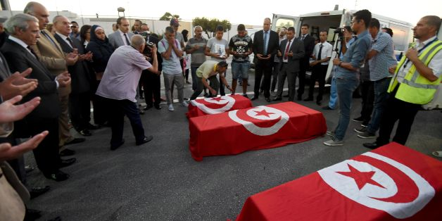 Tahar Mejri (back C) reacts as he stands in front of the flag-draped coffins of his four-year-old son (back) and wife Olfa Bent Souayah Khalfallah (C), who died in the Nice attack, after they arrived, along with the coffin of another victim Bilel Labbaoui, at the airport of Tunis-Carthage on July 19, 2016. / AFP / FETHI BELAID        (Photo credit should read FETHI BELAID/AFP/Getty Images)