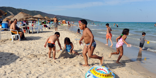 Children play on the beach in the Ghar El Melh suburb of Bizerte on July 1, 2012 as temperatures reached over 40 degreees Celcius over the weekend in Tunisia. AFP PHOTO : FETHI BELAID        (Photo credit should read FETHI BELAID/AFP/GettyImages)