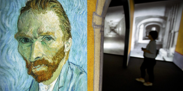 "A visitor walks past an image of Van Gogh's ""Self-Portrait"" during a press event for the world premiere of the Meet Vincent Van Gogh exhibit in Beijing, China, Wednesday, June 15, 2016. The exhibit, created by curators at the Van Gogh Museum, draws on Van Gogh's personal mementoes and artwork to present the artist's life. It opens to the public on June 18. (AP Photo/Mark Schiefelbein)"