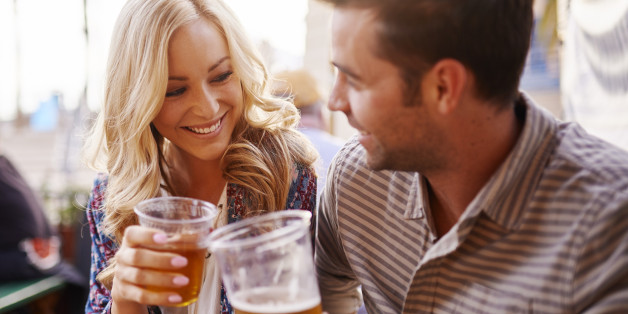 romantic couple drinking beer in plastic cups at outdoor bar with lens flare