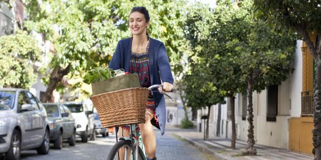 woman riding her bicycle on cobblestone street, basket full of fresh groceries