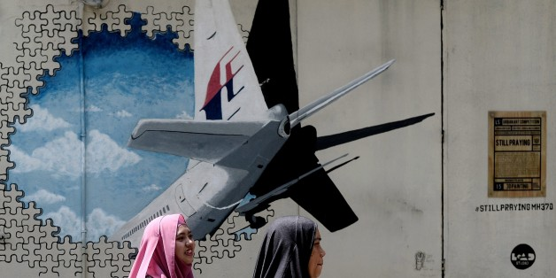 Malaysian women walk in front of a mural of missing Malaysia Airlines MH370 plane in a back-alley in Shah Alam on March 8, 2016. Malaysia and Australia said they remained 'hopeful' of solving the mystery of flight MH370 as the second anniversary of the plane's disappearance arrived March 8 with no end in sight for devastated families. / AFP / MANAN VATSYAYANA        (Photo credit should read MANAN VATSYAYANA/AFP/Getty Images)