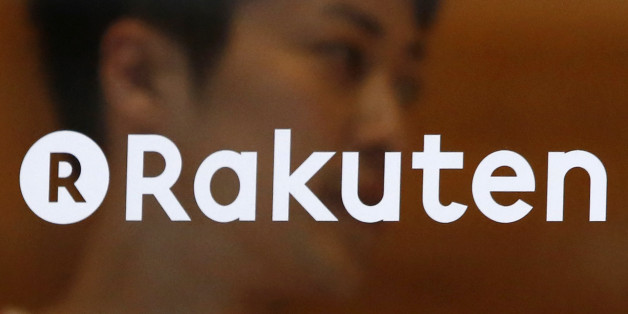 A staff of Rakuten Cafe is seen behind a logo of Rakuten Inc. at a shopping district in Tokyo August 4, 2014. Japan's largest e-commerce company Rakuten Inc posted a 9.9 percent decrease in second quarter operating profit, dragged lower by weaker trading volumes on its Internet finance platform. REUTERS/Yuya Shino (JAPAN - Tags: BUSINESS LOGO)