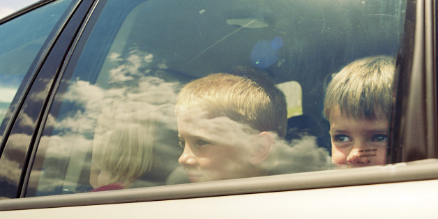Two boys (4-9) in car, looking through window