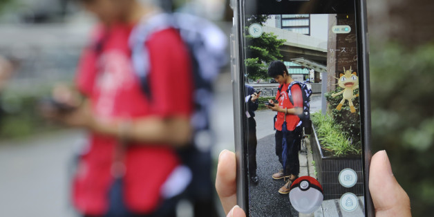 "Japanese students play ""Pokemon Go"" in the street as its released in Tokyo, Friday, July 22, 2016. ""Pokemon Go"" is expected to be a huge hit in Japan, the country of the character's birth. Fans have been eagerly awaiting its release since it first came out more than two weeks ago in Australia, New Zealand and the United States, and then became a blockbuster hit in more than 20 countries. (AP Photo/Koji Sasahara)"