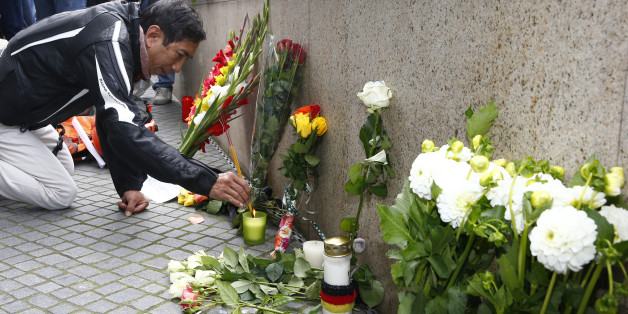 A man lights incense sticks near the Olympia shopping mall, where yesterday's shooting rampage started, in Munich, Germany July 23, 2016.  REUTERS/Arnd Wiegmann