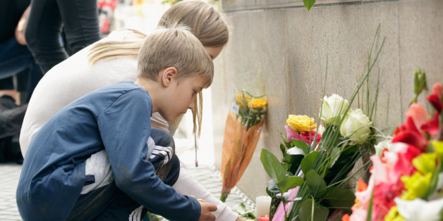 MUNICH, GERMANY - JULY 23:  People lay flowers and candles outside the OEZ shopping center the day after a shooting spree left nine victims dead on July 23, 2016 in Munich, Germany. According to police an 18-year-old German man of Iranian descent shot nine people dead and wounded at least 16 before he shot himself in a nearby park. For hours during the spree and the following manhunt the city lay paralyzed as police ordered people to stay off the streets. Original reports of up to three attacker