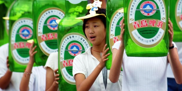 Young people hold balloon beer bottles of Tsingtao Beer during the opening ceremony of the 13th Qingdao International Beer Festival Friday, Aug. 15, 2003, at Beer City in Qingdao, China. The main attention of the festival this year is the local beer brand Tsingtao Beer, China's biggest beer company, which marked its centennial this year. (AP Photo/Eugene Hoshiko)