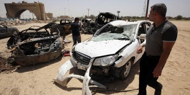 Des véhicules détruits lors d'un attentat suicide le 13 juillet 2016 à Bagdad