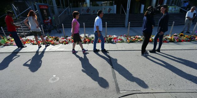 Picture taken on July 24, 2016 shows people standing at a memorial of candles and flowers laid down in front of the Olympia Einkaufszentrum shopping centre in Munich, southern Germany, where an 18-year-old German-Iranian student run amok. Europe reacted in shock to the third attack on the continent in just over a week, after David Ali Sonboly went on a shooting spree at a shopping centre on July 22, 2016 in what appears to have been a premeditated attack, before turning the gun on himself. / AFP / dpa / Karl-Josef Hildenbrand / Germany OUT        (Photo credit should read KARL-JOSEF HILDENBRAND/AFP/Getty Images)