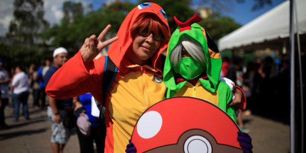 """Cosplayers dressed as characters of the augmented reality mobile game """"Pokemon Go"""" by Nintendo participate in a """"poketour"""" organized by the municipality in San Salvador, El Salvador July 23, 2016. REUTERS/Jose Cabezas"""