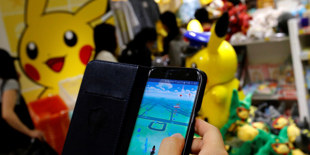 "A man plays the augmented reality mobile game ""Pokemon Go"" by Nintendo in front of a shop selling Pokemon goods in Tokyo, Japan July 22, 2016. REUTERS/Toru Hanai     TPX IMAGES OF THE DAY"