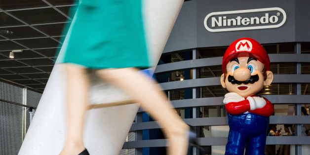 "A woman walks past a figure of ""Mario"", a character in Nintendo's ""Mario Bros."" video games, at a Nintendo centre in Tokyo July 29, 2015.  REUTERS/Thomas Peter/File Photo   GLOBAL BUSINESS WEEK AHEAD PACKAGE - SEARCH ""BUSINESS WEEK AHEAD JULY 25"" FOR ALL IMAGES"