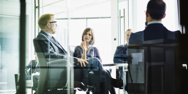 Female business executive leading meeting in office conference room