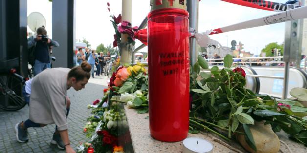 Eine Frau legt Blumen an den Tatort in München