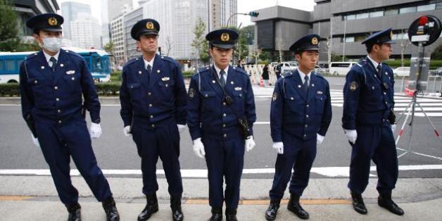 Ein japanischer Polizist riegelt den Tatort ab, im Hintergrund sind Retungswagen zu sehen