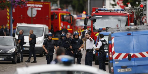 French police officers and fire engine arrive at the scene of a hostage-taking at a church in Saint-Etienne-du-Rouvray, northern France, on July 26, 2016 that left the priest dead.A priest was killed on July 26 when men armed with knives seized hostages at a church near the northern French city of Rouen, a police source said. Police said they killed two hostage-takers in the attack in the Normandy town of Saint-Etienne-du-Rouvray, 125 kilometres (77 miles) north of Paris. / AFP / CHARLY TRIBALLE