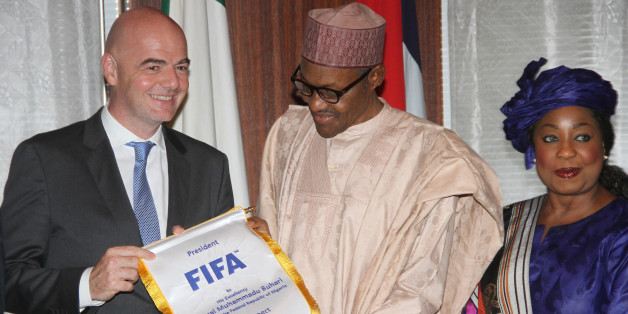 FIFA President Gianni Infantino (L) presents a souvenir to Nigerian President Mohammadu Buhari as FIFA Secretary General Fatma Samoura stands (R) during his visit to the presidency in Abuja, on July 25, 2016. Infantino, who is on a two-day working visit to Nigeria with FIFA secretary General Fatma Samoura, visited President Mohammadu Buhari alongside Football Association (FA) presidents from other African countries. / AFP / PHILIP OJISUA        (Photo credit should read PHILIP OJISUA/AFP/Getty I
