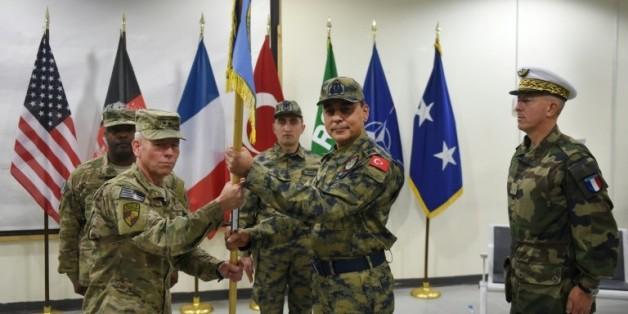 Le général turc Mehmet Cahit Bakir entre le commandant américain John McMullen et le général français Philippe Lavigne, lors d'une cérémonie de remise de drapeau le 31 décembre 2014 à Kaboul