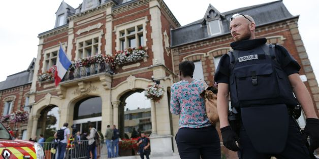 A French police officer stands guard by Saint-Etienne-du-Rouvray's city hall following a hostage-taking at a church in Saint-Etienne-du-Rouvray, northern France, on July 26, 2016 that left the priest dead.A priest was killed on July 26 when men armed with knives seized hostages at a church near the northern French city of Rouen, a police source said. Police said they killed two hostage-takers in the attack in the Normandy town of Saint-Etienne-du-Rouvray, 125 kilometres (77 miles) north of Paris