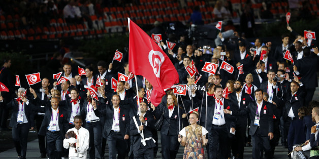 Tunisia's flag bearer Heykel Megannem holds the national flag as he leads the contingent in the athletes parade during the opening ceremony of the London 2012 Olympic Games at the Olympic Stadium July 27, 2012. REUTERS/Mike Blake (BRITAIN  - Tags: SPORT OLYMPICS)