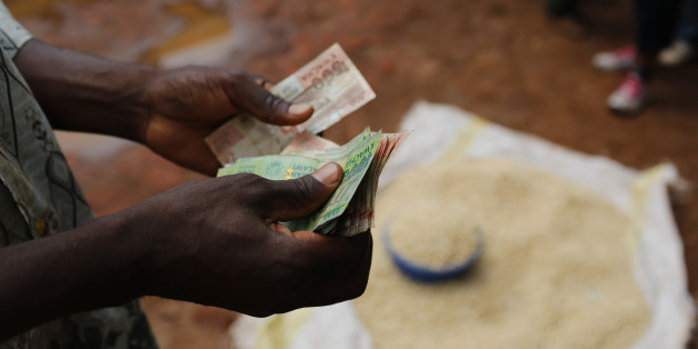 A Malawian trader counts money as he sells maize near the capital Lilongwe, Malawi February 1, 2016. Floods and an El Nino-triggered drought have hit the staple maize crop, exposing the fragility of Malawi's progress, which was partly rooted in a fertiliser grant for small-scale farmers that the government, now starved of donor funds, can ill afford. Picture taken February 1, 2016. To match Insight AFRICA-DROUGHT/MALAWI. REUTERS/Mike Hutchings