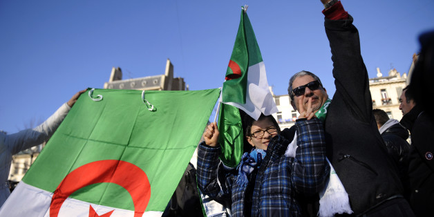 People hold Algerian flags on January 22, 2011 in Marseille, southern France, in support of local pro-democracy demonstrations in Algeria. The Algerian League for the Defence of Human Rights (LADDH) said today the blanket government ban on peaceful protest could cause a social explosion in the North African country, eight days after ousted leader Zine El Abidine Ben Ali fled Tunisia following violent street protests. AFP PHOTO / ANNE-CHRISTINE POUJOULAT (Photo credit should read ANNE-CHRISTINE P