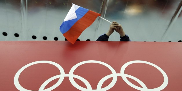FILE - In this Feb. 18, 2014 file photo, a Russian skating fan holds the country's national flag over the Olympic rings before the start of the men's 10,000-meter speedskating race at Adler Arena Skating Center during the 2014 Winter Olympics in Sochi, Russia. The IOC's ruling 15-member executive board will meet Sunday, July 24, 2016 via teleconference to weigh the unprecedented step of excluding Russia as a whole from the 2016 Rio Olympic Games because of systematic, state-sponsored cheating. (