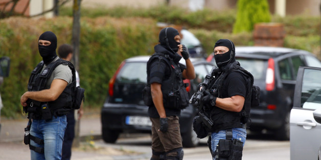 Police officers conduct a search in Saint-Etienne-du-Rouvray, Normandy, France, following an attack on a church that left a priest dead, Tuesday, July 26, 2016. Two attackers invaded a church Tuesday during morning Mass near the Normandy city of Rouen, killing an 84-year-old priest by slitting his throat and taking hostages before being shot and killed by police, French officials said. (AP Photo/Francois Mori)