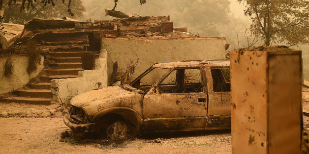 A burned car rests in front of a Palo Colorado area residence leveled by the Soberanes Fire near Big Sur, California, U.S. July 26, 2016.  REUTERS/Noah Berger