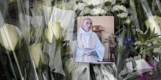 A picture of late Father Jacques Hamel is placed on flowers at the makeshift memorial in front of the city hall closed to the church where an hostage taking left a priest dead the day before in Saint-Etienne-du-Rouvray, Normandy, France, Wednesday, July 27, 2016. The Islamic State group crossed a new threshold Tuesday in its war against the West, as two of its followers targeted a church in Normandy, slitting the throat of an elderly priest celebrating Mass and using hostages as human shields be