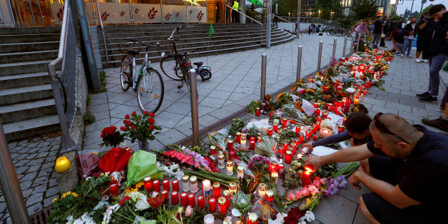 People light candles beside flowers laid in front of the Olympia shopping mall, where yesterday's shooting rampage started, in Munich, Germany July 23, 2016. REUTERS/Arnd Wiegmann