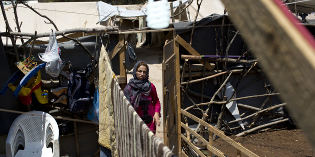 A Syrian woman enters the makeshift courtyard of her family's tent at Ritsona refugee camp north of Athens, which hosts more than 600 refugees and migrants, on Thursday, July 14, 2016. Over 57,000 migrants and refugees remain stranded in Greece following European border closures. The European Union is pressing member states to speed up implementation of its refugee settlement scheme, amid delays in negotiations with Turkey for visa-free travel _ promised by Brussels as part of a deal to limit migrant travel to Europe. (AP Photo/Petros Giannakouris)