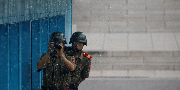 North Korean soldiers keeps watch toward the south as it rains during a ceremony marking the 63rd anniversary of the signing of the Korean War ceasefire armistice agreement at the truce village of Panmunjom, South Korea, July 27, 2016.  REUTERS/Kim Hong-Ji